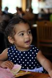 Black Bi-Racial Toddler Female. African-American, Bi-racial toddler female in restaurant with a coloring menu stock photo