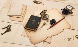 Black bible book and vintage accessories. With old cards and papers Stock Photos