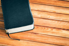 Black Bible on Wooden Surface. Detail of a black Bible on a wooden surface with copy space Royalty Free Stock Image