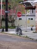 Black bicycle at corner of road by red stop sign royalty free stock photos