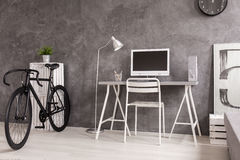 Black bicycle in grey and white living room. Grey modern living room with white desk and shelf. Next to it black sports bicycle Royalty Free Stock Photo