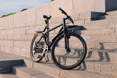 Black bicycle stands on the stone steps Royalty Free Stock Photography