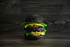 Black Big Mac with fresh vegetables and juicy cutlet. Big beautiful juicy burger with meat and vegetables Stock Photos