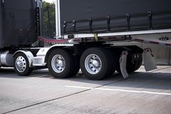 Black big rig semi truck with chrome wheels and fenders and black tented frame semi trailer going by roadway. Fragment of stylish powerful well maintained black royalty free stock photo