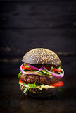 Black big sandwich - black hamburger with juicy beef burger, cheese, tomato, and red onion Stock Photography