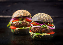 Black big sandwich - black hamburger with juicy beef burger, cheese, tomato, and red onion Royalty Free Stock Photos