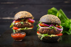 Black big sandwich - black hamburger with juicy beef burger, cheese, tomato, and red onion Royalty Free Stock Photo