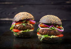 Black big sandwich - black hamburger with juicy beef burger, cheese, tomato, and red onion Stock Images