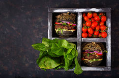 Black big sandwich - black hamburger with juicy beef burger, cheese, tomato, and red onion in box Stock Image