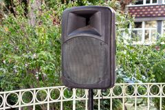 Black big speaker on stand outdoor / A big p.a. speaker on a stage at an outdoor music festival / Large audio speaker. Black big speaker on stand outdoor / A Stock Image