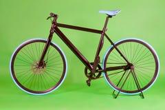 Black bike. Black commuter urban bike on green background. Studio shoot Stock Images