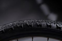 Black bike tire with water drops on abstract background. Biking theme Stock Photo