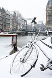 Black bike wheel in snow in Amsterdam with canal and bridge Stock Photos