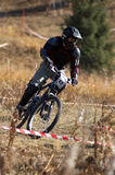 Black biker on race. Black mountain biker on downhill race Royalty Free Stock Photo