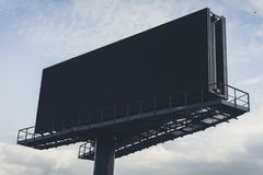 Black billboard against bright blue sky. Stock Photos