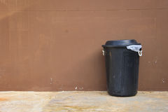 Black bin and wall on road Stock Photos