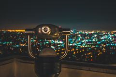 Black Binocular Facing Lighted City at Nighttime Stock Photo