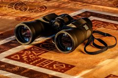 Black Binoculars in Maroon and Beige Textile Stock Images