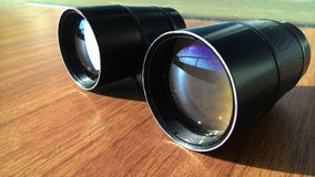Black binoculars on the table. Black binoculars lie on the table in sunny weather. In the mirror transparent glass, the street is beautifully reflected.Jpeg Royalty Free Stock Images