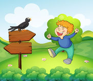 A black bird above the wooden sign near a young boy Royalty Free Stock Photo