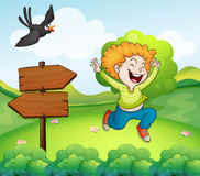 A black bird and a happy boy near the arrow signage Stock Images