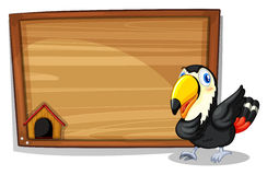 A black bird beside a wooden blank board Stock Images