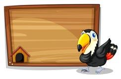 A black bird beside a wooden blank board Stock Images