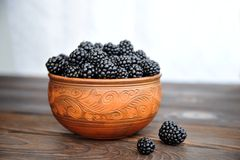 Black blackberries in clay ware on a table royalty free stock images