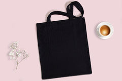 Black blank cotton eco tote bag, design mockup. Black blank cotton eco tote bag with baby breath flower and cup of coffee on a pink background, design mockup Royalty Free Stock Photo