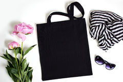 Black blank cotton eco tote bag, design mockup. Black blank cotton eco tote bag with pink peony, glasses and scarf, design mockup Royalty Free Stock Photos