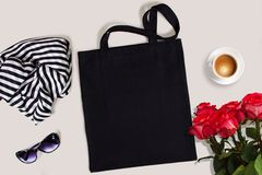 Black blank cotton eco tote bag with red roses, glasses, scarf and a cup of coffee, styled design mockup stock photo