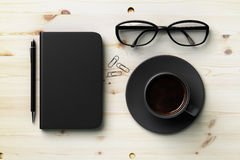 Black blank diary cover, black cup of coffee and glasses on wood Stock Image