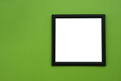 Black blank picture frame on greenery color paint wall background. stock photos