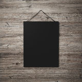Black blank poster hanging on leather belt on wood background Royalty Free Stock Photography
