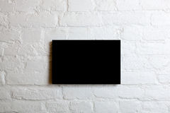 Black blank poster in a white brick wall. Template Mock up for your content Stock Image
