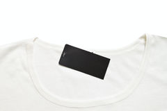 Black blank price tag hang over white tshirt. Stock Photo