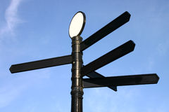 Black blank signpost. Against a blue sky Stock Image