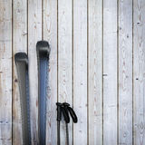 Black blank skis on wooden planks wall, winter background Stock Photos