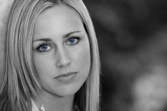 Black And Blue. Black and white shot of a beautiful young woman with bright blue eyes and an enigmatic smile Stock Photos