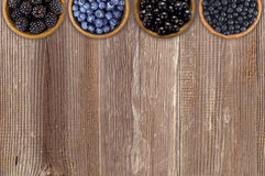 Black and blue berries. Blackberries, blueberries, currants and blueberries in a wooden bowls Royalty Free Stock Photography