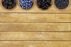 Black and blue berries. Blackberries, blueberries, currants and blueberries in a wooden bowls. Berries at border of image with copy space for text. Top view Royalty Free Stock Photos