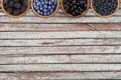 Black and blue berries. Blackberries, blueberries, currants and blueberries in a wooden bowls on a wooden background. Berries at border of image with copy Royalty Free Stock Photos