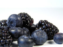 Black and blue berries in a pile. Closeup of blueberries and blackberries isolated on white in a pile royalty free stock photo