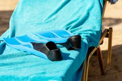 Black and Blue Diving Flippers on a Deck Chair. Pair of a black and blue diving flippers fins on a blue towel on a deck chair at the beach stock image