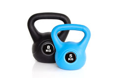 Black and blue kettlebells on white background. A pair of black 8 kg kettlebell and 5 kg blue kettlebell isolated on white background. Weights for a fitness Royalty Free Stock Photos