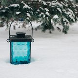 Black and blue lantern on the snow against snow-covered branches.Beautiful winter background, copy space. Black and blue lantern on the snow against snow-covered royalty free stock photos