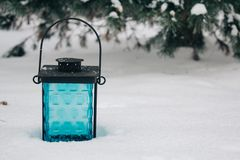 black and blue lantern on the snow against snow-covered branches.Beautiful winter background, copy space royalty free stock photo