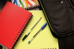 Black and Blue Pens Beside Red Covered Notebook Stock Image