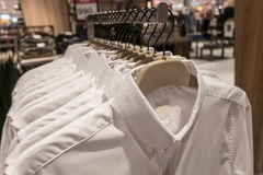 Black and blue shirt hang on the rack, Men`s shirts on hangers in wardrobe. White and blue shirt hang on the rack, Men`s shirts on hangers in wardrobe Stock Images