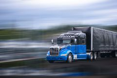 Black and blue stylish big rig semi truck transporting commercial cargo in covered black semi trailer. Stylish black and blue big rig long haul semi truck with royalty free stock photos